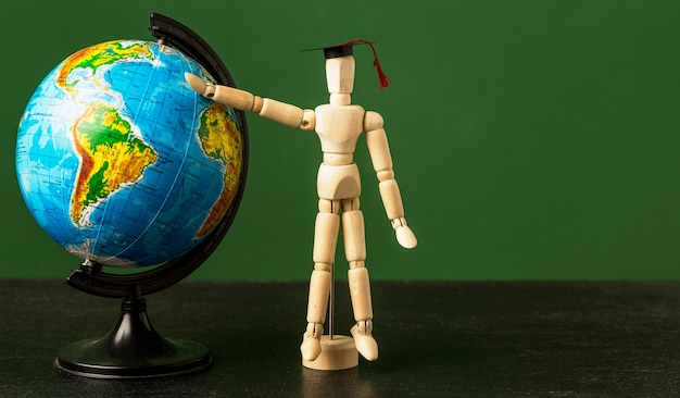 Front view of wooden figurine with academic cap and earth globe