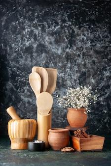 Cucchiai di legno di vista frontale con pentole e cannella sul muro scuro foto condimenti a colori sale posate per alimenti