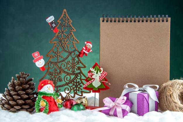 おもちゃの松ぼっくりノートブックの小さなギフトボックスと正面図の木製のクリスマスツリー