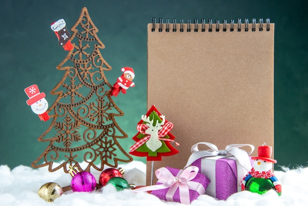 Vista frontale albero di natale in legno con giocattoli pigna blocco note piccoli regali