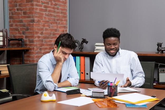 Vista frontale dei colleghi del processo di lavoro che hanno trattative commerciali in un ufficio moderno