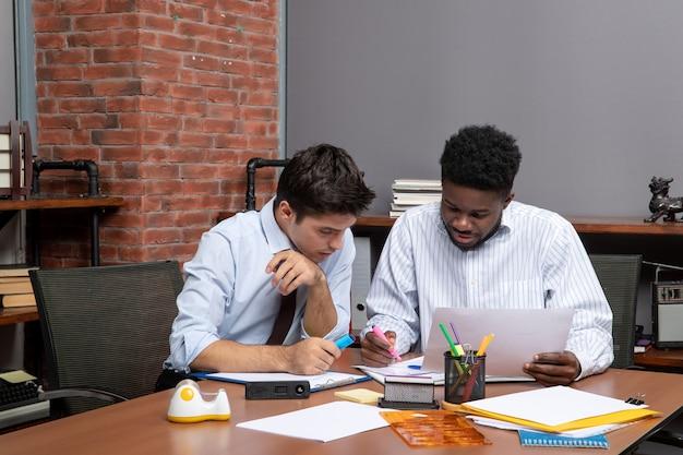 Vista frontale del processo di lavoro di due uomini d'affari che discutono di un progetto mentre sono seduti alla scrivania