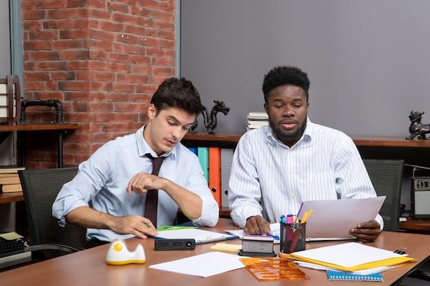 正面図の作業プロセスオフィスで働くフォーマルウェアの2人のビジネスマン