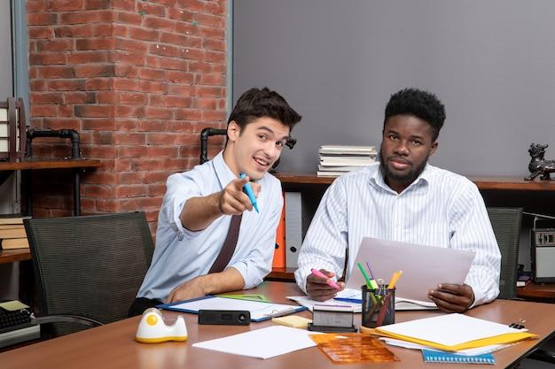 Processo di lavoro vista frontale due uomini d'affari seduti alla scrivania uno di loro che punta con la fotocamera del dito