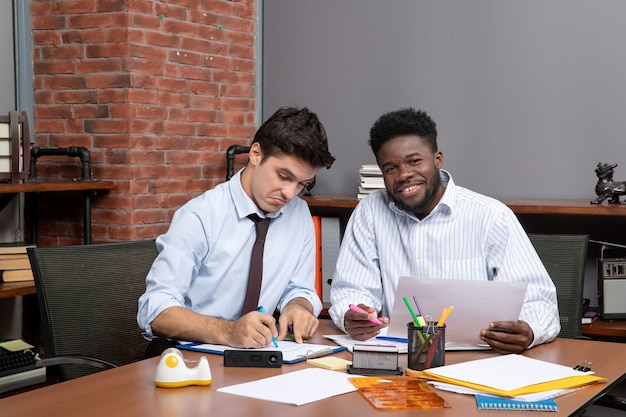 Front view work process two businessmen sitting at the desk sock photo