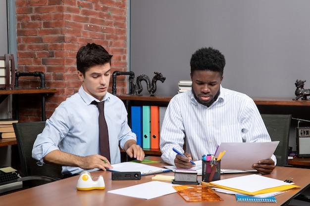 전면 보기 작업 프로세스 사무실에서 일하는 두 명의 자신감 있는 사업가