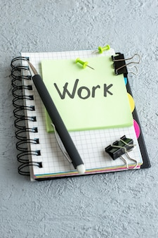 Вид спереди работа письменная записка на зеленой наклейке с блокнотом и ручкой на белой поверхности цветная работа офис школа тетрадь бизнес колледжа Бесплатные Фотографии