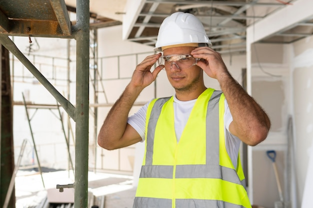 Front view worker in construction wearing protection gear