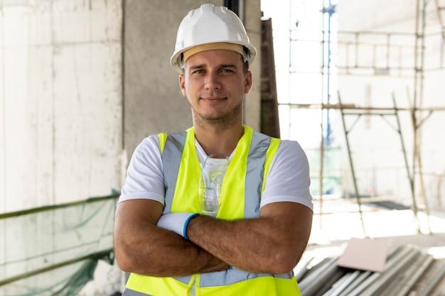 保護具を身に着けている建設中の正面図の労働者