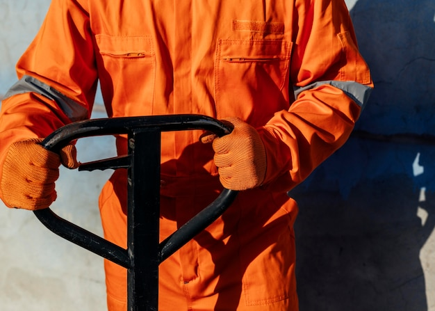 Lavoratore di vista frontale in uniforme con guanti protettivi che maneggiano carrello elevatore