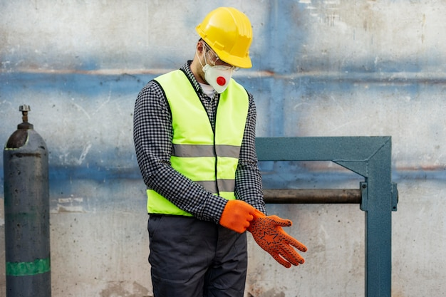 Front view of worker with hard hat putting on protective gloves