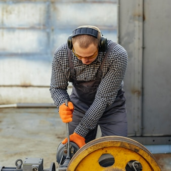 Front view of worker with protective gloves and headphones