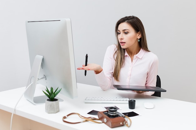 Front view of working woman looking at computer and not understanding what's going on