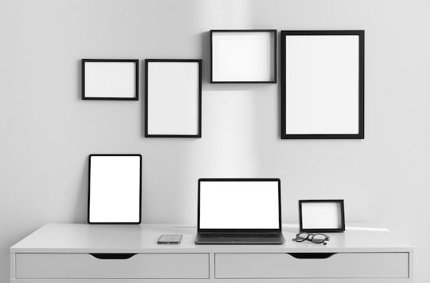 Vista frontale della superficie della scrivania sul posto di lavoro con laptop e cornici