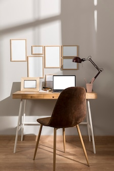 Front view of workspace desk surface with laptop and chair