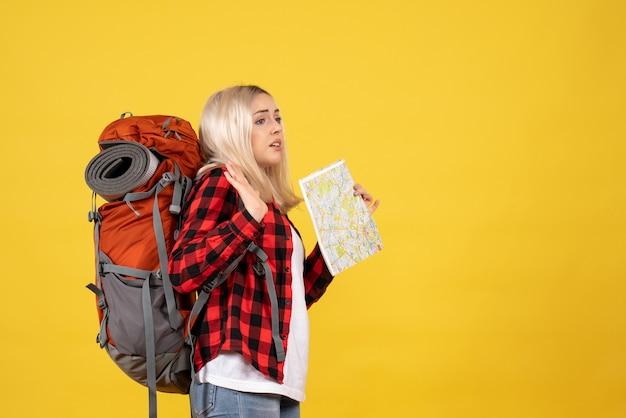 Вид спереди взволнованная блондинка с рюкзаком держит карту
