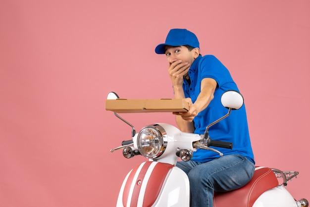 Vista frontale del corriere preoccupato che indossa un cappello seduto su uno scooter che tiene l'ordine su sfondo color pesca pastello