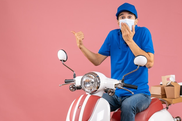 Vista frontale del ragazzo delle consegne preoccupato in maschera medica che indossa un cappello seduto su uno scooter su sfondo color pesca pastello