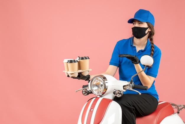 Vista frontale della donna preoccupata per le consegne che indossa maschera medica e guanti seduto su uno scooter che tiene ordini su sfondo color pesca pastello