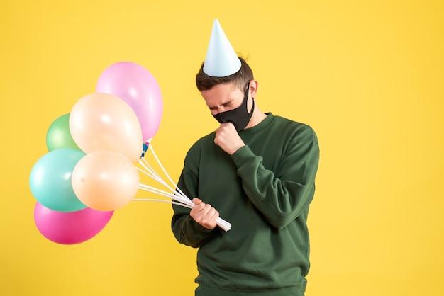 Vista frontale preoccupato giovane uomo con cappello da festa e palloncini colorati in piedi sul giallo