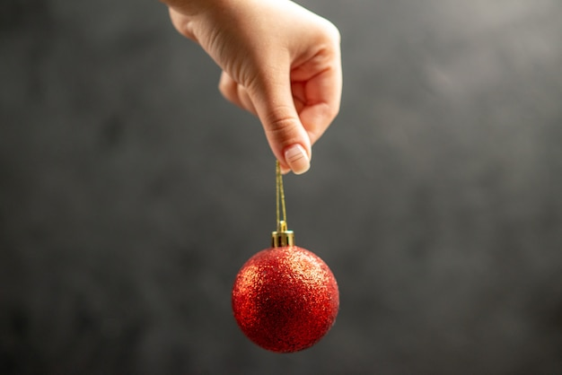 暗い自由空間に女性の手で正面図のクリスマスボール