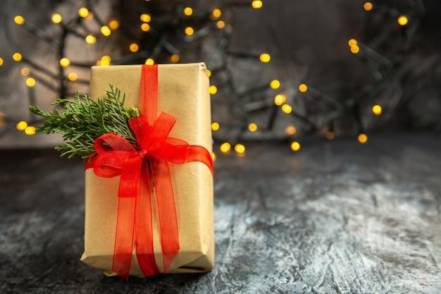 暗い背景のクリスマスライトに赤いリボンで結ばれた正面図のクリスマスプレゼント