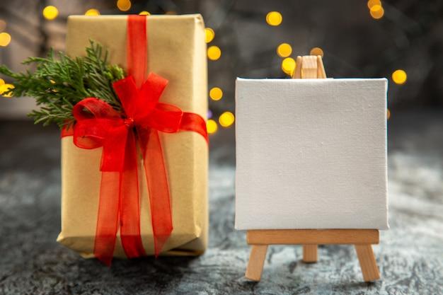 Рождественский подарок, вид спереди, перевязанный красной лентой, белый холст на деревянном мольберте, рождественские огни на темноте