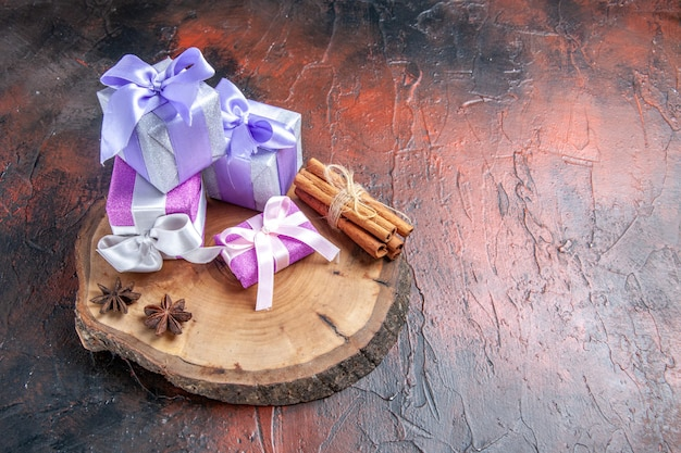 Front view xmas gifts anises cinnamon on tree cutting board on dark red background with free space