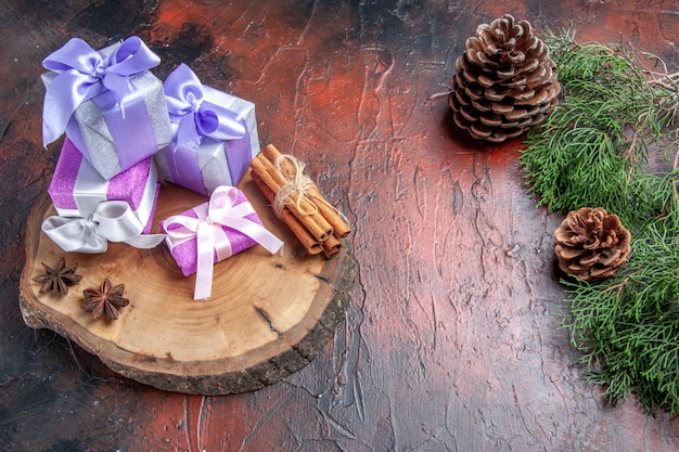 Front view xmas gifts anises cinnamon on tree cutting board pine tree branch with cones on dark red background