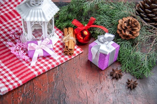 正面図クリスマスギフト松の木の枝とコーンクリスマスボールおもちゃランタン赤いテーブルクロス濃い赤の背景クリスマス写真