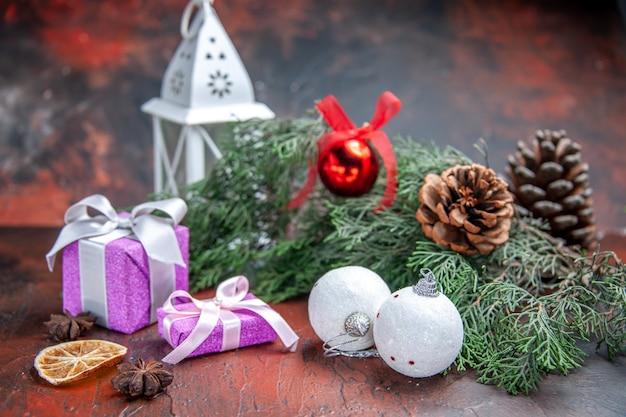 Vista frontale regali di natale rami di pino con coni palla di natale giocattoli lanterna su foto di natale rosso scuro