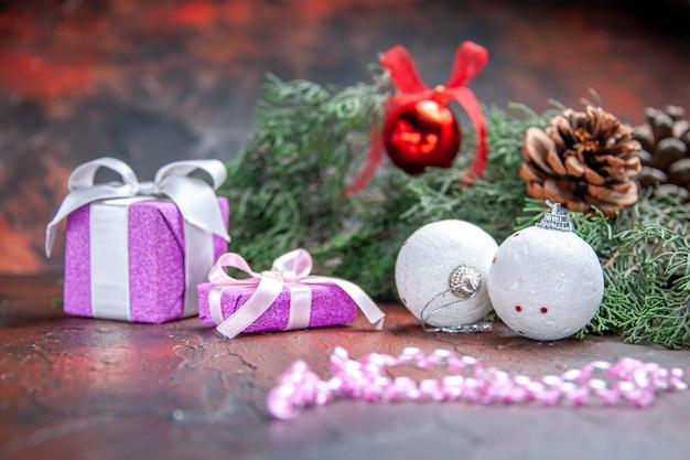 Vista frontale regali di natale rami di pino natale palla giocattoli su sfondo rosso scuro isolato foto di natale x