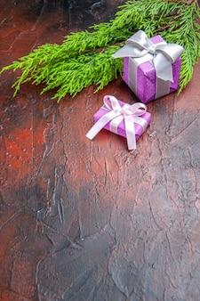 コピースペースと濃い赤の背景にピンクのボックスと白いリボンの木の枝と正面のクリスマスプレゼント