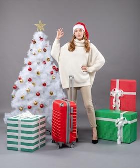 白いクリスマスツリーと赤いvaliseの近くに立っているオーケーサインを作る正面のクリスマスの女の子