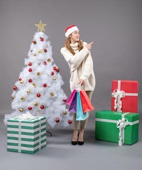 カラフルな買い物袋が正しい方向を示して見ている正面図のクリスマスの女の子