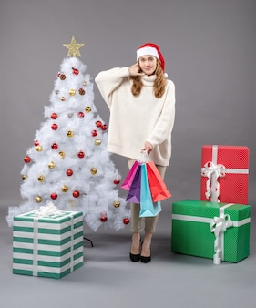 Front view xmas girl with colorful shopping bags showing call me phone sign