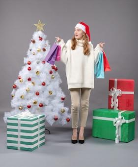 左方向を見てカラフルな買い物袋を保持しているサンタ帽子と正面のクリスマスの女の子