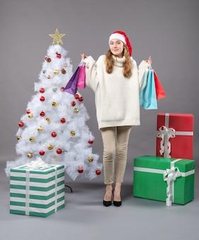 正しい方向を見ているカラフルな買い物袋を保持しているサンタ帽子と正面のクリスマスの女の子