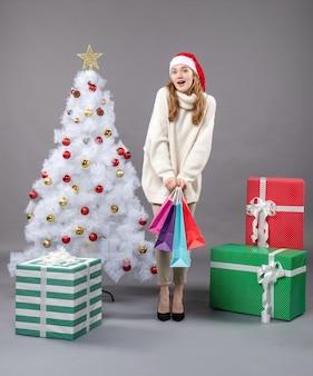 カラフルな買い物袋を保持しているサンタの帽子と正面のクリスマスの女の子
