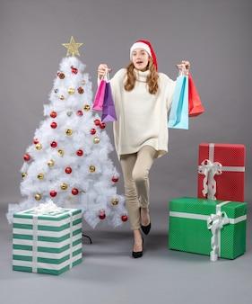 クリスマスツリーの近くに多くの買い物袋を保持しているサンタ帽子を持つ正面のクリスマスの女の子 無料写真