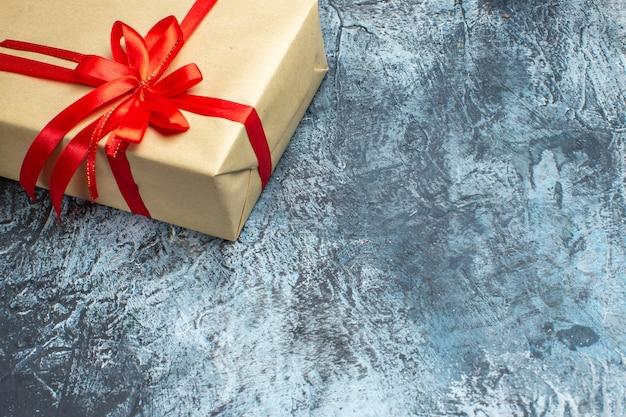 Vista frontale regalo di natale legato con fiocco rosso su foto di vacanza chiaro-scuro colore natale capodanno spazio libero