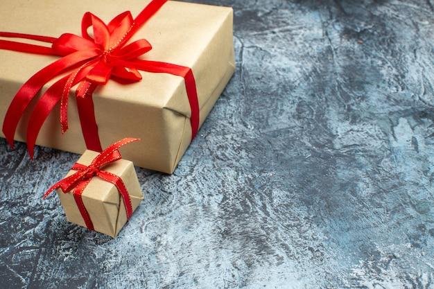 Vista frontale regalo di natale legato con fiocco rosso su foto di vacanza chiaro-scuro colore di natale capodanno