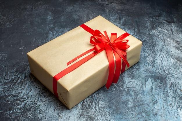 Рождественский подарок, вид спереди, перевязанный красным бантом на светло-темном праздничном фото, рождественский цвет, новый год