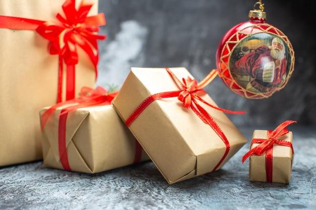 Vista frontale regali di natale legati con fiocchi rossi sulla foto del regalo di natale delle vacanze di capodanno di colore chiaro-scuro