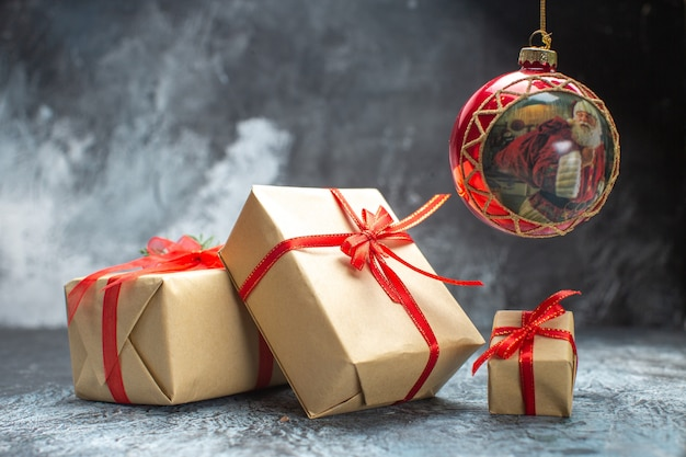 Vista frontale regali di natale legati con fiocchi rossi su foto a colori chiari e scuri regali di natale per le vacanze di capodanno