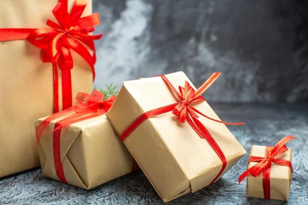 Vista frontale regali di natale legati con fiocchi rossi su foto a colori chiaro-scuro vacanze di capodanno regalo di natale