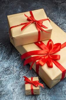 Vista frontale regali di natale legati con fiocchi rossi su foto di vacanza chiaro-scuro colore natale capodanno