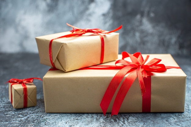 Vista frontale regali di natale legati con fiocchi rossi sul regalo di natale di colore di festa della foto di capodanno chiaro-scuro