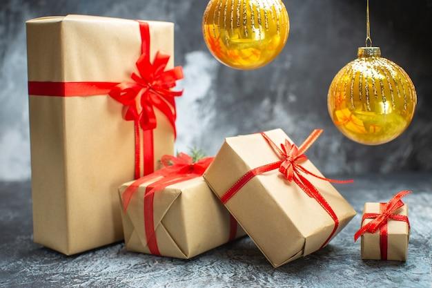 正面から見たクリスマス プレゼントは、明るい暗い色の新年の休日のクリスマス ギフトの写真に赤いリボンで結ばれています。