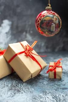 正面から見たクリスマス プレゼントは、明るい暗い色の写真の新年の休日のクリスマス プレゼントに赤いリボンで結ばれています